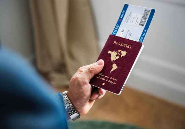 selective focus photography of person holding passport with ticket