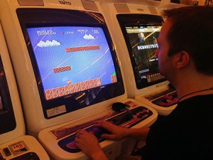Kai playing Super Mario Bros on an arcade machine.