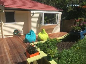 View from the hill towards the deck, with plants in the front and two beanbags on the deck.