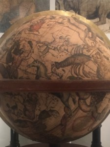 Globe with various animals painted on it, including a unicorn.