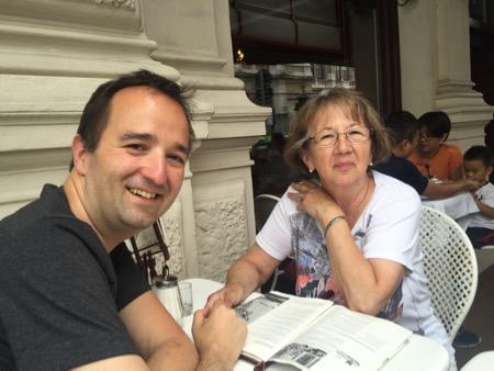 Kai and Inge sitting at a table, waiting for their Sachertorte (cake).