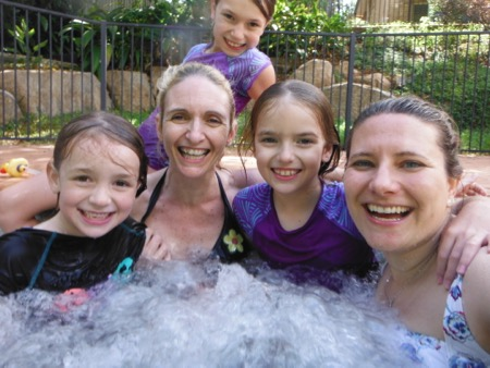 Diane, Meggy and her 3 daughters in a jacuzzi, all smiling into the camera.