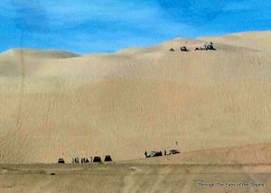 Sand dunes with dune buggies in the distance. taken from car window