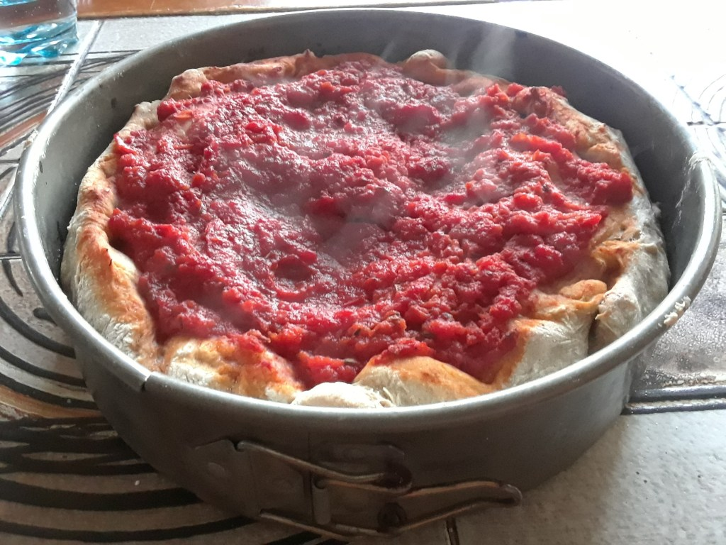 Chicago-style deep dish pizza, still steaming from the oven