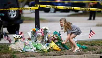 Niña deposita ramo de flores en memorial in situ en Virginia Beach