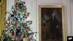 Un árbol decorado se encuentra junto al retrato del presidente George Washington en la Sala Este durante la vista previa de Navidad de 2019 en la Casa Blanca, el lunes 2 de diciembre de 2019, en Washington. (Foto AP / Alex Brandon).