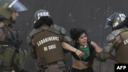 Policías antidisturbios detienen a un estudiante que participaba en las protestas en Santiago.