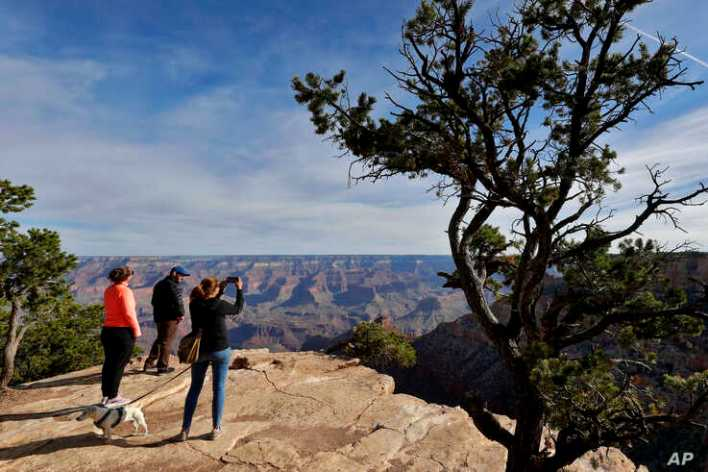 Tanya Wyler takes a photograph as Matthias Zather and Ines Zather, all of Switzerland, gather at the Grand Canyon Friday, May…