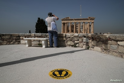 A visitor takes a photo of the Parthenon temple next to a social distancing marker, as the Acropolis archaeological site opens…