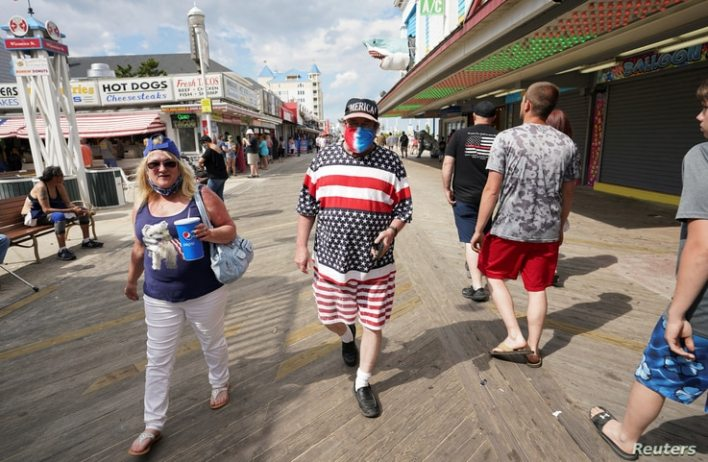 With the coronavirus disease (COVID-19) restrictions eased, a man dressed in stars and stripes for Memorial Day weekend walks…