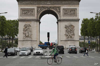 A person rides his bicycle in front of Arc de Triomphe, Monday, May 11, 2020 in Paris. he French began leaving their homes and…