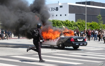 A person runs while a police vehicle is burning during a protest over the death of George Floyd in Los Angeles, Saturday, May…