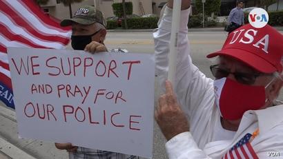 4: Dos manifestantes posan junto a un cartel con el mensaje