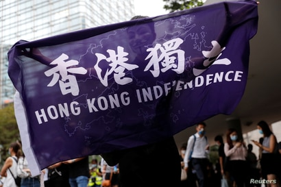 A pro-democracy demonstrator holds a flag supporting Hong Kong Independence during a protest to mark the first anniversary of a…