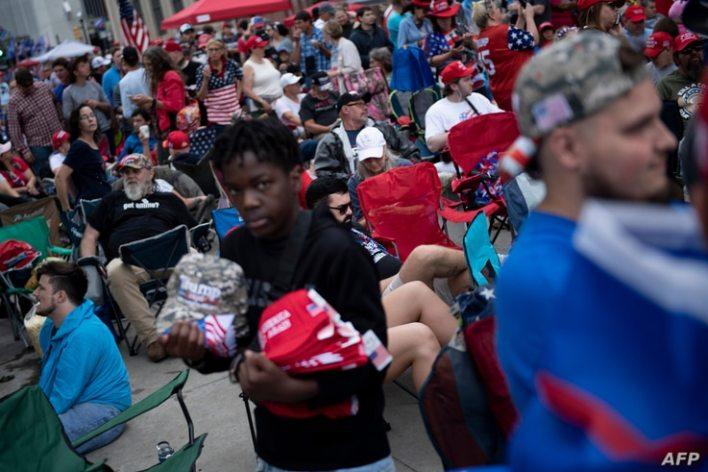 A vender sells memorabilia as people wait to attend a rally with US President Donald Trump this evening at the BOK Center on…