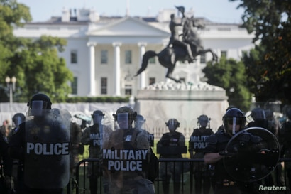 DC National Guard military police officers look on as demonstrators rally near the White House against the death in Minneapolis…