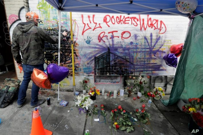 An artist at left works on a piece using spray paint and chalk, Tuesday, June 30, 2020, next to a growing memorial for a 16…