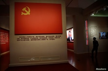 A staff member wearing a face mask stands near an exhibit of a flag of Chinese Communist Party at the National Museum in…