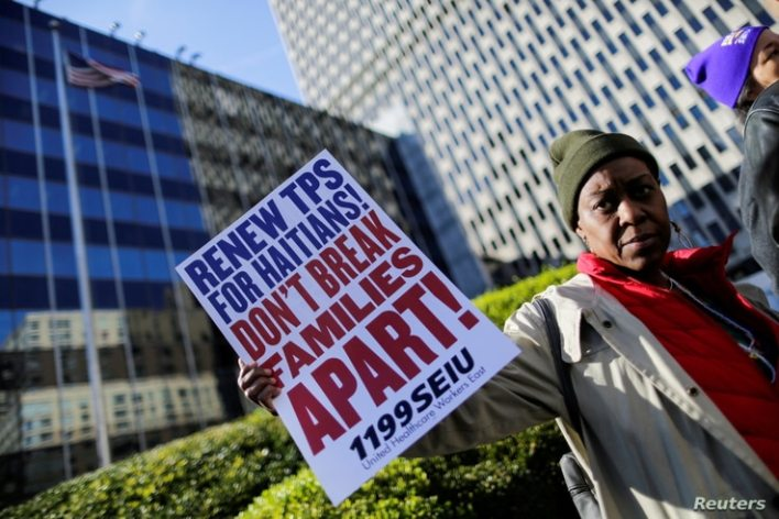 FILE PHOTO: A woman holds a placard as Haitian immigrants and supporters rally to reject DHS Decision to terminate TPS for Haitians, at the Manhattan borough in New York