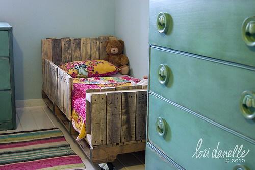 Cama de bebé con barandas hecha con palets reciclados