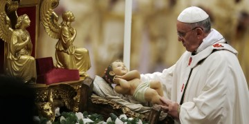 Pope Francis holds a statue of baby Jesus as he celebrates the Christmas Eve Mass in St. Peter's Basilica at the Vatican, Tuesday, Dec. 24, 2013. (AP Photo/Gregorio Borgia)