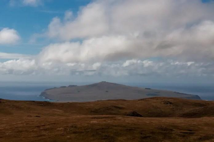 Montanhas, vales, nuvens e o azul marinho do Oceano Pacífico com sua linha reta dividindo o mundo em dois