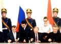 Un grupo de personas observan un discurso del presidente ruso, Vladimir Putin, ante la Asamblea Federal en Sevastopol