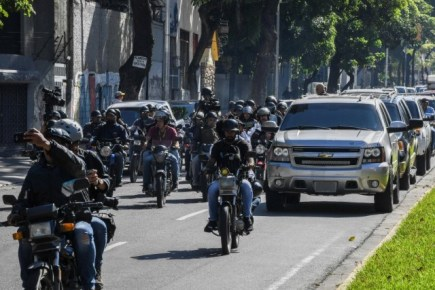 """A caravan carrying Venezuelan opposition leader and self-proclaimed acting president Juan Guaido, followed by motorized journalists, heads to the National Assembly, in Caracas, on January 7, 2020. - Opposition leader Juan Guaido and a rival lawmaker, Luis Parra -who both had claimed to be Venezuela's parliament speaker, following two separate votes and accusations of a """"parliamentary coup- called for a parliamentary session. (Photo by YURI CORTEZ / AFP)"""
