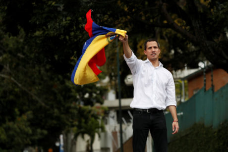 Venezuelan opposition leader Juan Guaido, who many nations have recognised as the country's rightful interim ruler, waves the Venezuelan flag as he speaks to supporters near Bolivia's embassy in Caracas, Venezuela, November 16, 2019. REUTERS/Carlos Garcia Rawlins