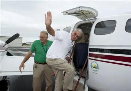 El alcalde de Key West Craig Cates se despide al subir a un vuelo chárter en el Aeropuerto Internacional de Key West con destino a La Habana el lunes 30 de diciembre de 2013 en una fotografía proporcionada por Florida Keys News Bureau. El viaje fue el primer vuelo comercial y legal de Key West a Cuba en más de 50 años. (Foto AP/Florida Keys News Bureau)