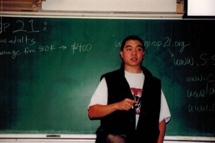 Image of my younger self with long hair pulled back doing a workshop on Proposition 21. I'm wearing a vest and standing in front of a chalk board.