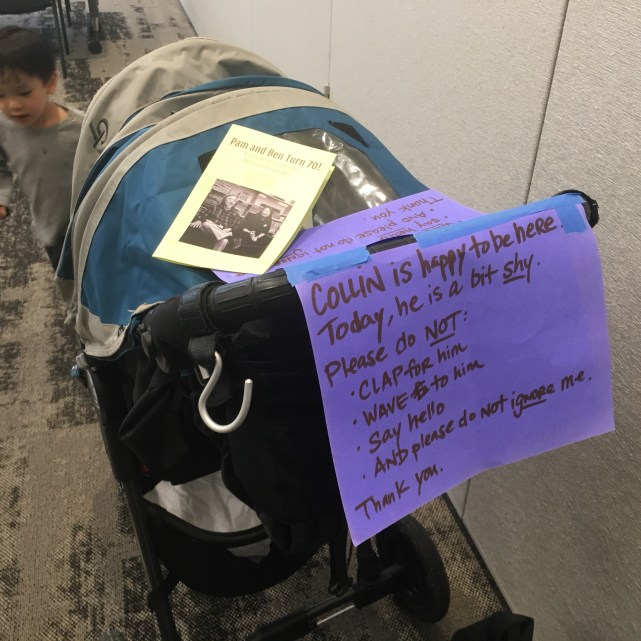 Image of the stroller with the sign in the play room. Collin is pictured running