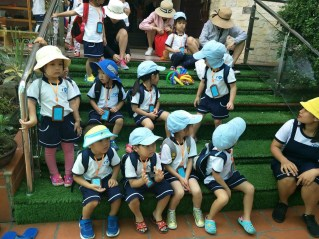 Photo of all the students in uniform sitting on stairs at the zoo field trip.