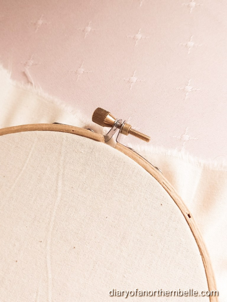 tightly secured fabric in embroidery hoop showing screw mechanism