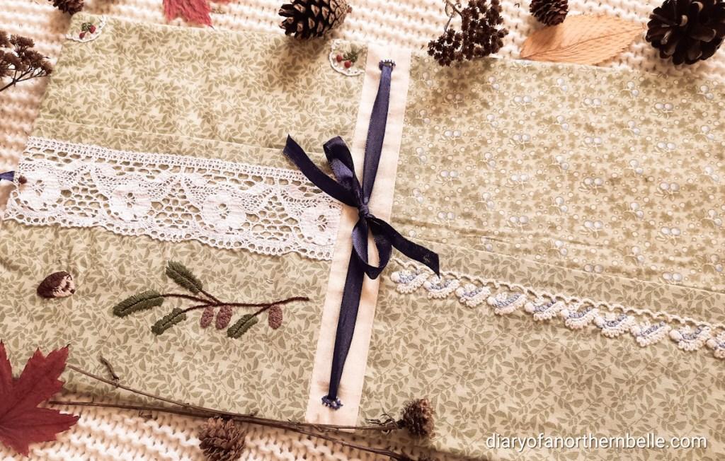 "open view of stitch book, showing dark blue ribbon threaded through book ""spine"""