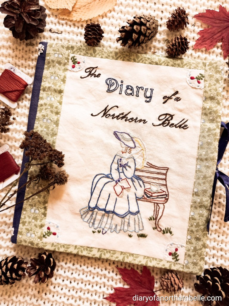 """flat lay of the embroidered front cover of the stitch book, featuring a """"Sounthern belle"""" lady on a bench with books and a cup of tea beside her, grass at her feet, and the words """"Diary of a Northern Belle"""" stitched in cursive above her. In all four corners of the cover are stitched little red berries surrounded by a white scalloped edge."""