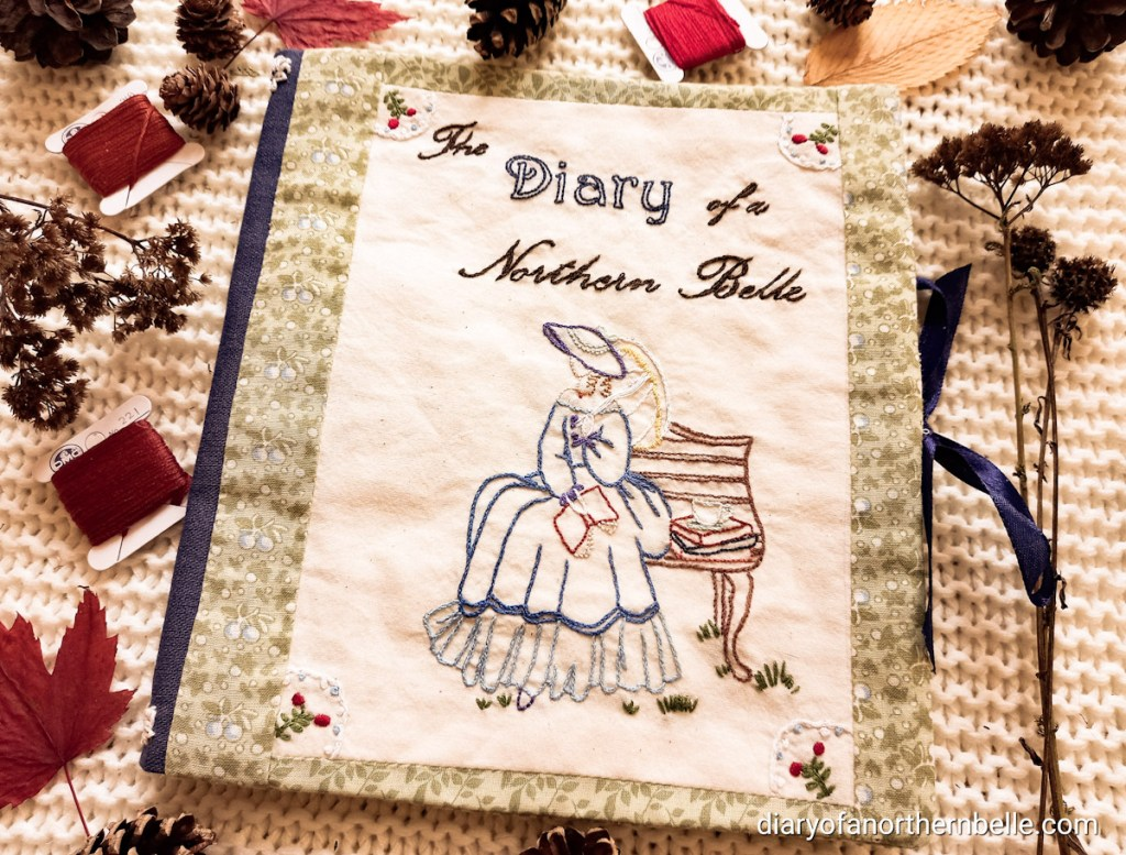 flat lay view of closed stitchbook showing embroidered front cover. Stitchbook is surrounded by pinecone props and other dried flowers, as well as winded red floss and red autumn leaves