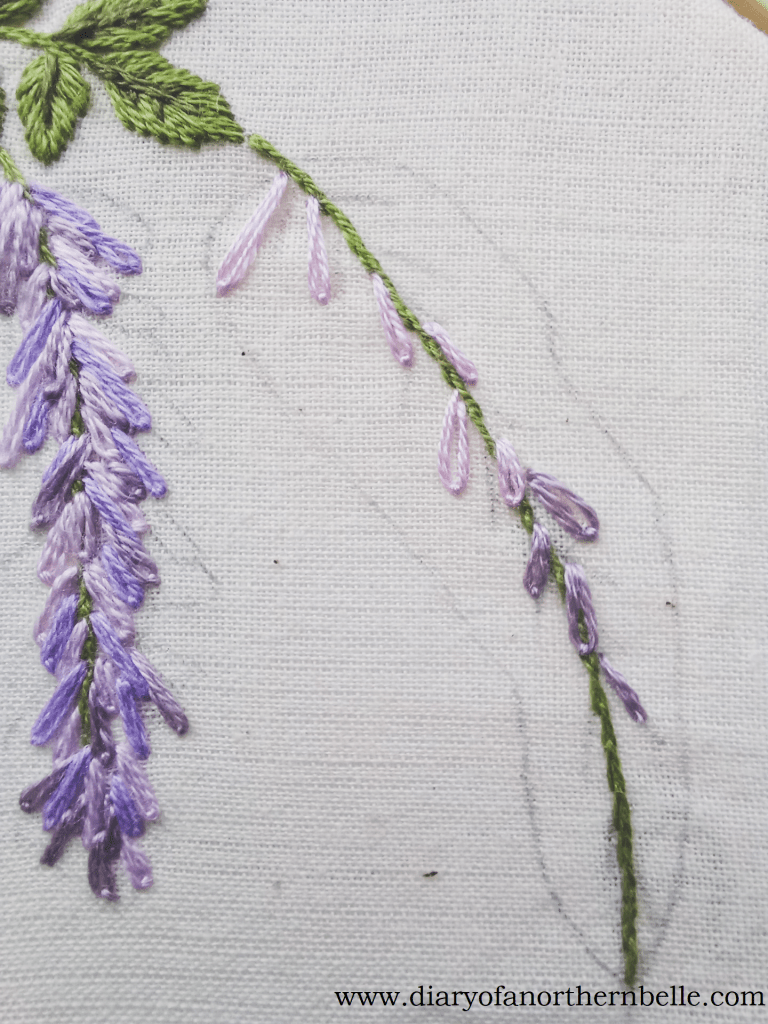 lazy-daisy stitches embroidered along wisteria branch to create flowers