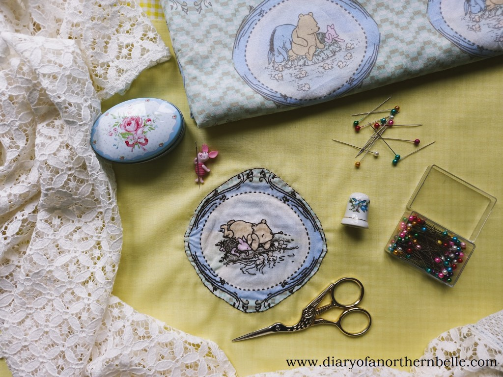 Embroidered Winnie-the-Pooh patch surrounded by sewing tools and pooh fabric