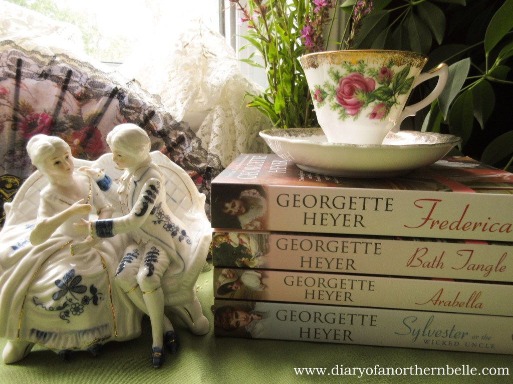 stack of books by inspiring author Georgette Heyer with bone china teacup and porcelain figurine of two lovers on a settee