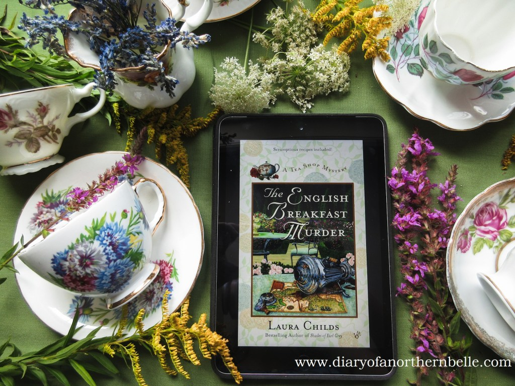bookcover of the English Breakfast Murder by inspiring author Laura Childs on iPad surrounded by bone china teacups and wildflowers