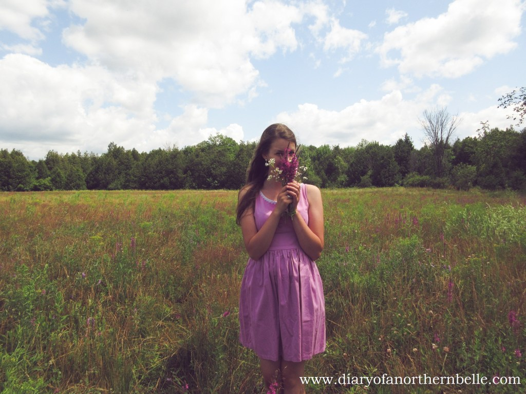 girl in field wearing lilac dress holding flower bouquet up to her face