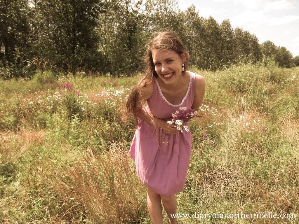 model wearing lilac dress in field leaning forward with flower bouquet