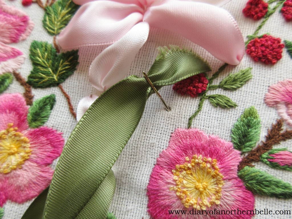making a straight stitch with green ribbon for the leaves