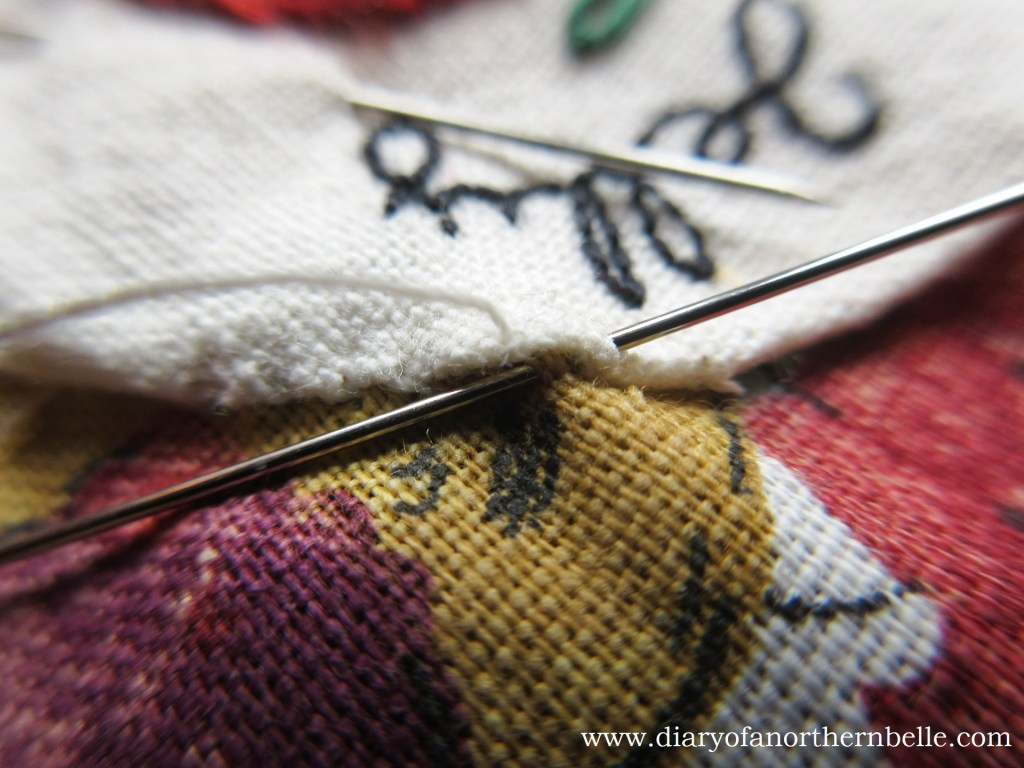 appliqué being sewed down with whipstich