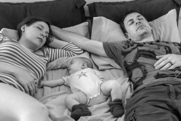Baby lying in bed with parents.