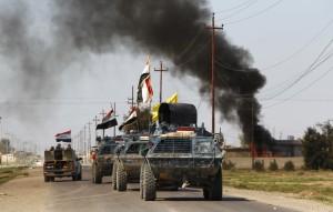 Mjete të korracuara të forcave të sigurisë së Irakut me milicinë e njohur si Hashid Shaabi po udhëtojnë mes tymit që ngrihet nga përleshjet me militantët e shtetit Islamik në qytezën al-Alam më 10 mars 2015. REUTERS/Thaier Al-Sudani