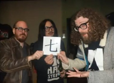 """Beards and long hair holding up the Chinese character for """"7"""" in a Death to Giants music video."""