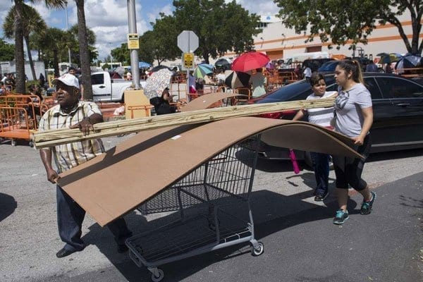 People push a cart full of wood and supplies outside a Home Depot store in Miami, Florida, as they prepare for Hurricane Irma on September 7, 2017. PHOTO | SAUL LOEB | AFP