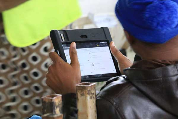An IEBC official holds a KIEMS gadget during